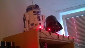 Bastel-D2 und Bastel-Vader auf einem bereits für Weihnachten geschmückten Bücherregal.